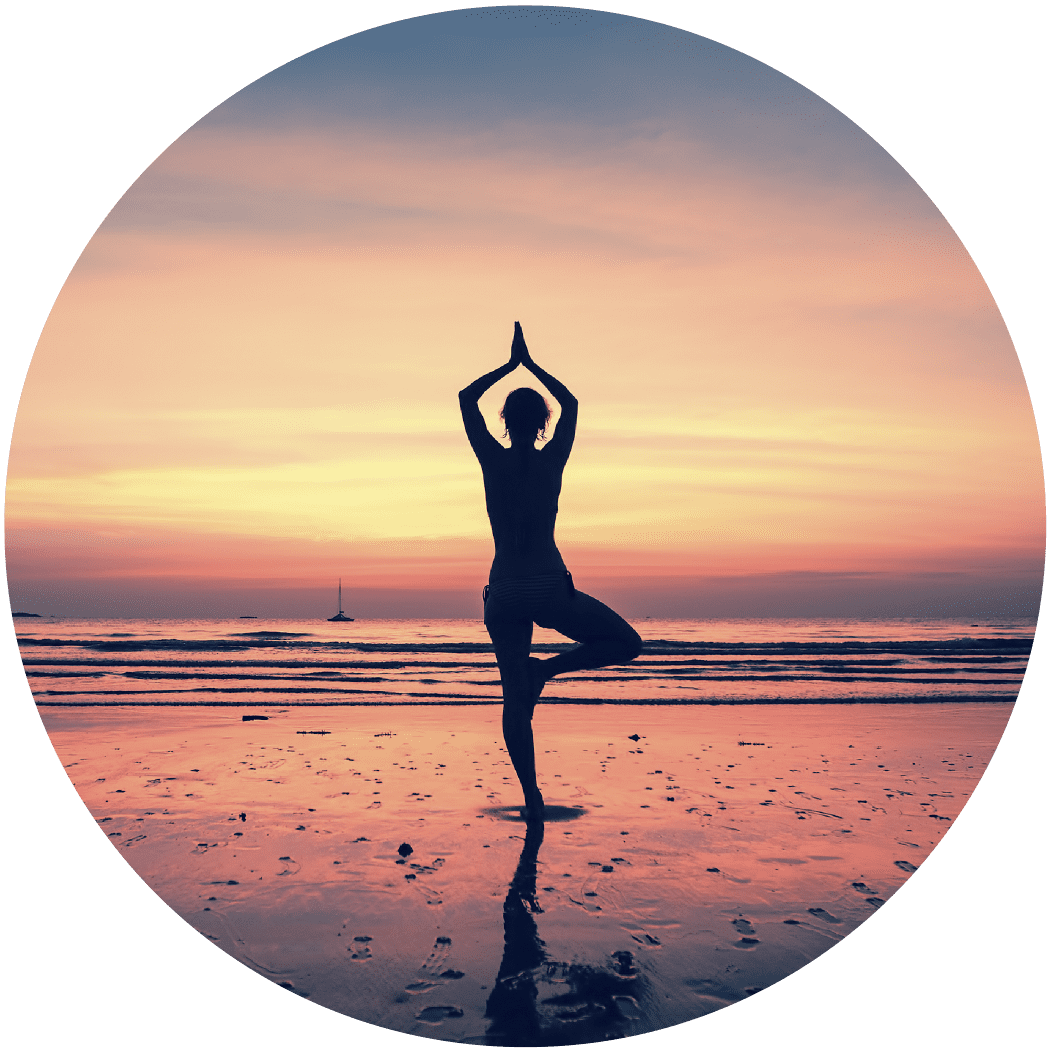 Woman in yoga pose on beach in front of sunset sky.